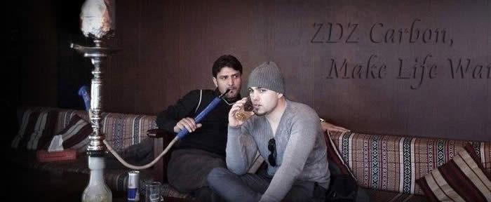 一个男的在抽阿拉伯水烟单管壶,一个男的在喝酒